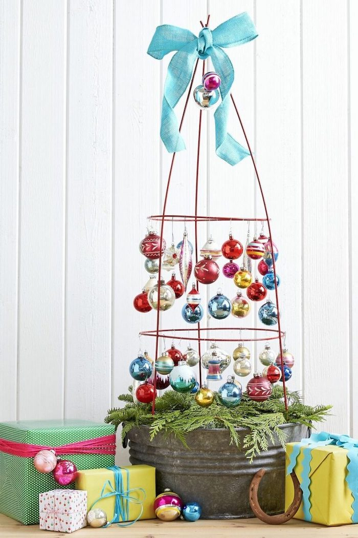 tomato cage with baubles and blue ribbon on top, christmas porch decorations, wrapped presents underneath, white background