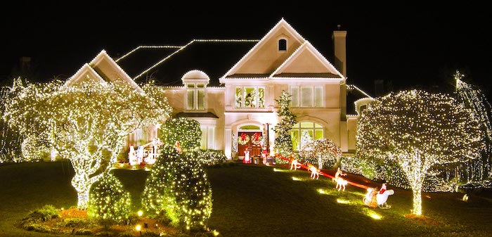 two storey house, decorated with lights, christmas porch decorations, lots of trees and bushes, decorated with lights