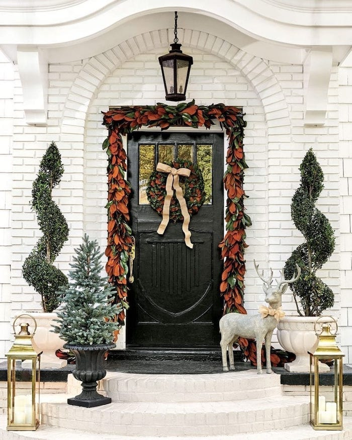 wreath with fall leaves, hanging over door frame, front porch christmas decorations, trees and lanterns on both sides
