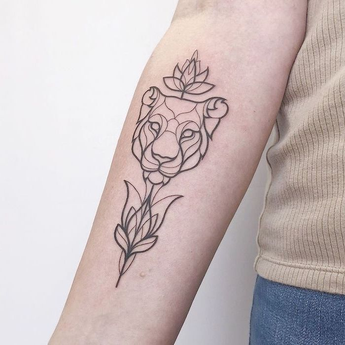 lion king tattoo, forearm tattoo, on woman wearing jeans and beige top, geometrical contoured lion head with lotus flowers