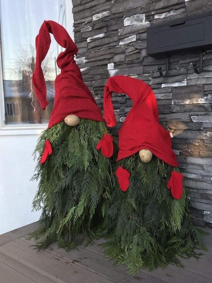 gnomes made of tree branches, red hats and gloves, front porch christmas decorations, placed on wooden porch