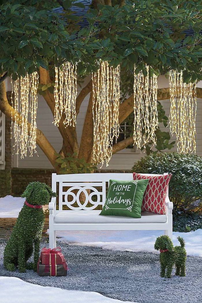 strings of fairy lights, hanging from tree, front porch christmas decorations, over a wooden bench with throw pillows
