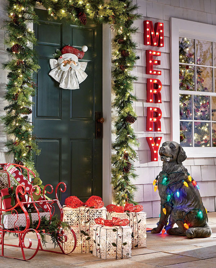 wreath over the door frame, sled and led presents arranged on the porch, yard decorations, dog figurine with lights
