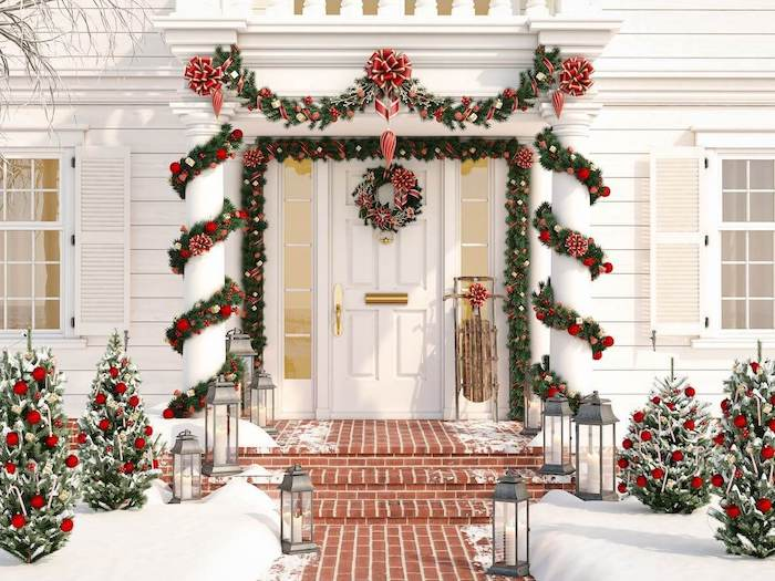 wreaths with red baubles and ribbons, hanging all around the front door, yard decorations, decorated trees on both sides