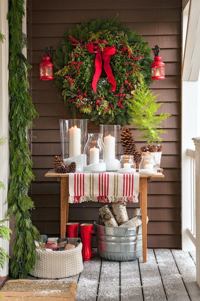 green wreath with berries, hanging over wooden table, candles and pine cones on it, outdoor lighted christmas decorations