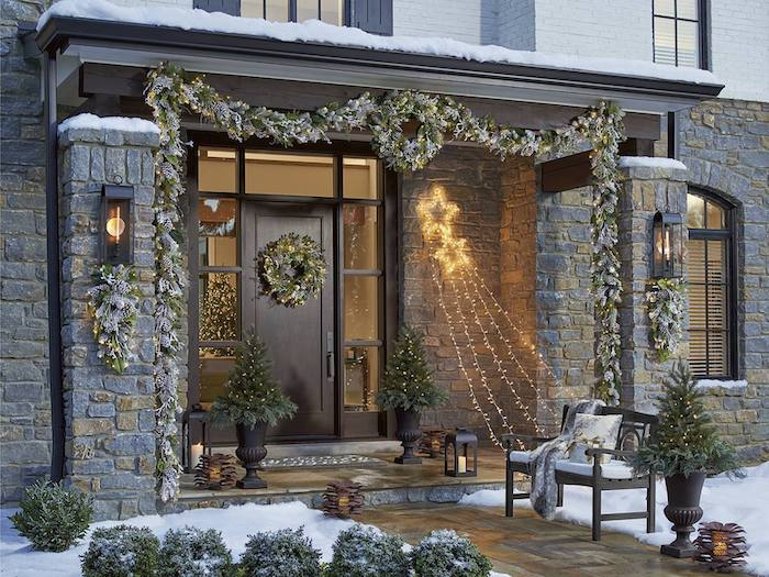 wreaths hanging on the door and door frame, outdoor lighted christmas decorations, strings of lights hanging from the wall to a bench