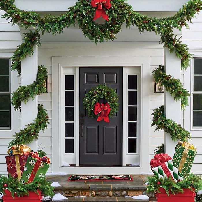 wreaths with lights and red ribbons, hanging on door and door frame, front porch christmas decorations, presents figurines on both sides