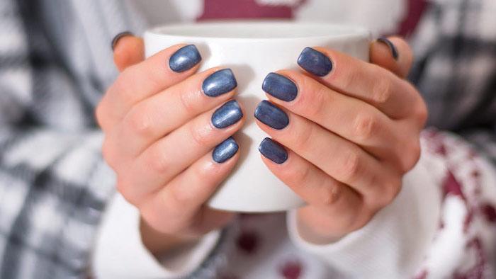 two hands holding a mug, short squoval nails, winter nails, blue glitter nail polish