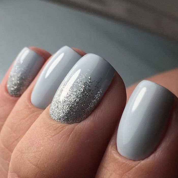 light grey nail polish, winter nail designs, silver glitter on pinky and middle finger, short squoval nails