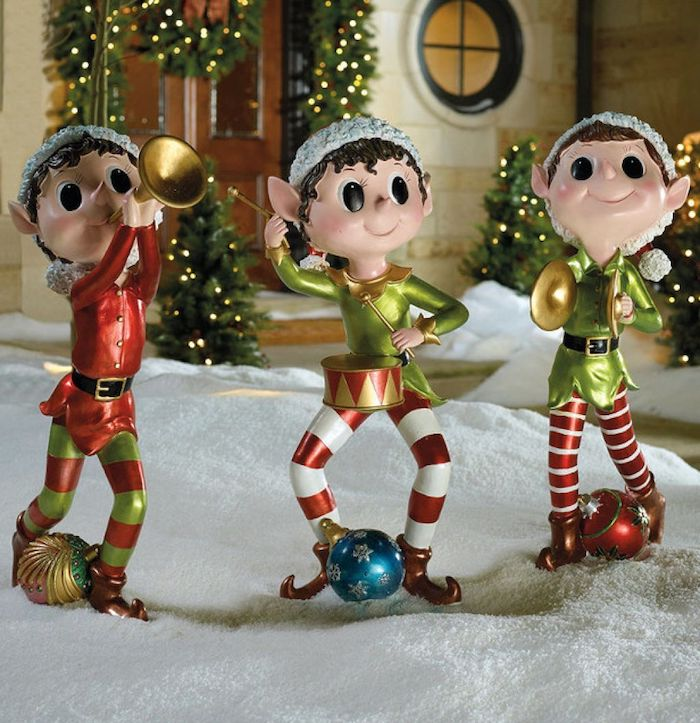 three elf figurines, placed in the snow in front of a house, diy outdoor christmas decorations, door decorated with wreaths with lights