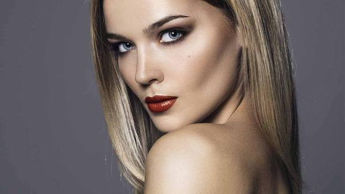 woman with blonde hair, dark red lipstick, brunette highlights, long straight hair, grey background
