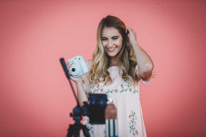 woman holding an instant camera, wearing pink floral dress, brunette highlights, long wavy brown hair with blonde balayage