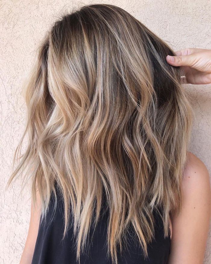 hair highlights ideas, balayage dark blonde hair with highlights, medium length wavy hair, woman wearing black top