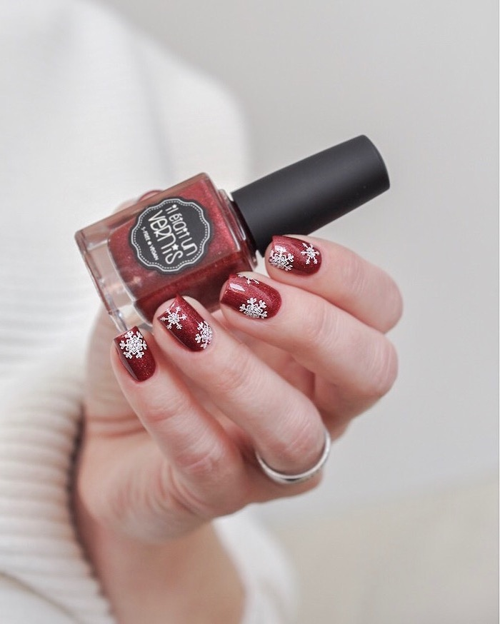 hand holding red nail polish bottle, short square nails with red nail polish, snowflakes decorations on each nail, winter nails