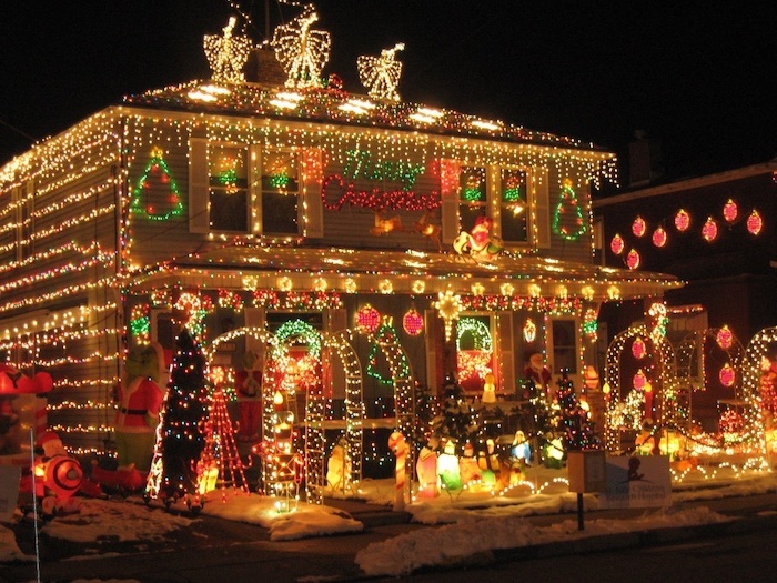 two storey house, decorated with lots of lights, front door christmas decor, lots of lighted figurines in the front yard