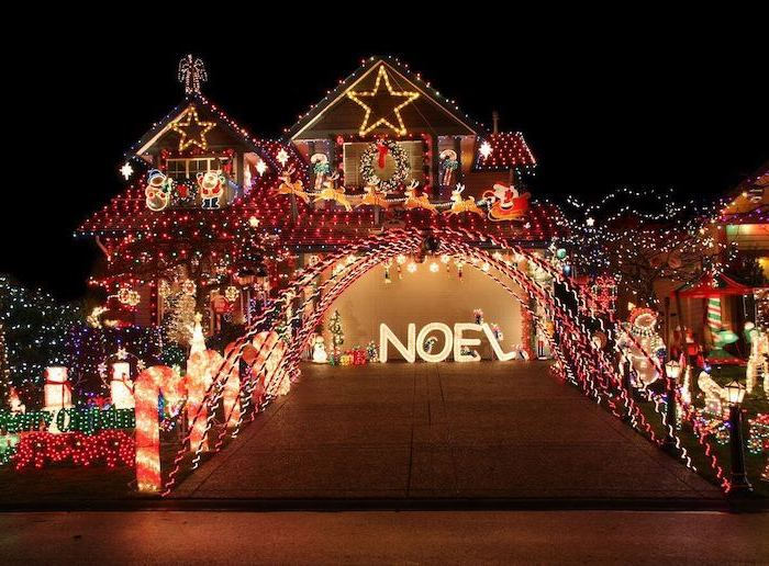 two storey house decorated with lights, front door christmas decor, lots of lighted figurines in the front yard, along the pathway
