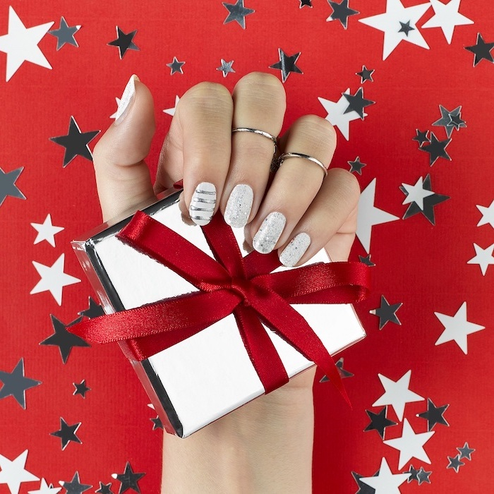hand holding a wrapped present with red ribbon, winter nails, white and silver glitter nail polish, medium length squoval nails