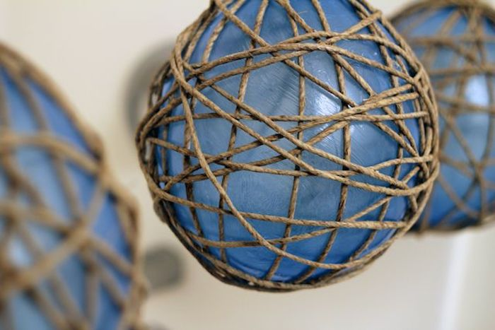 blue balloons, twine wrapped around them, outdoor christmas decorations ideas, step by step diy tutorial