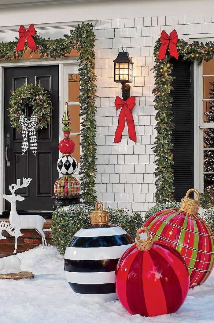 wreaths with red ribbons, hanging over the door and window frames, outdoor lighted christmas decorations, large baubles in the snow