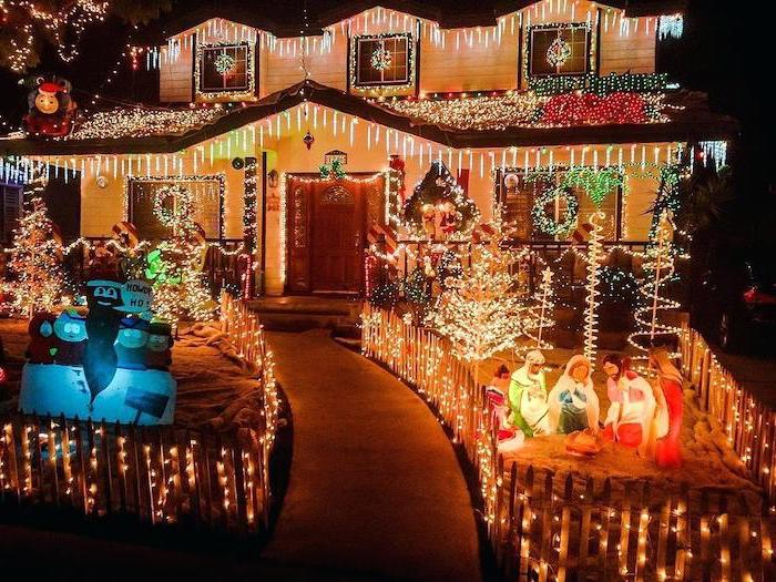large two storey house, covered with lights, lots of lighted figurines int he front yard, front door christmas decor