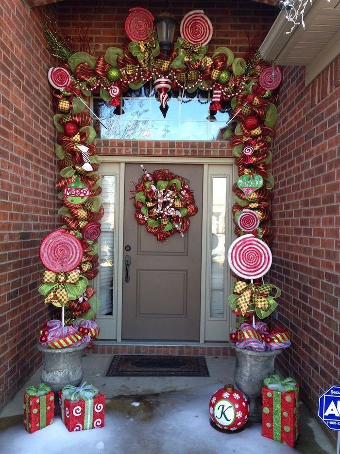 wreath made of green and red ribbons, hanging on door and door frame, outdoor lighted nativity scene, wrapped presents on both sides