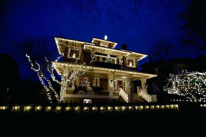 large two storey house, covered with lights, outdoor lighted nativity scene, trees covered with lights in the front yard