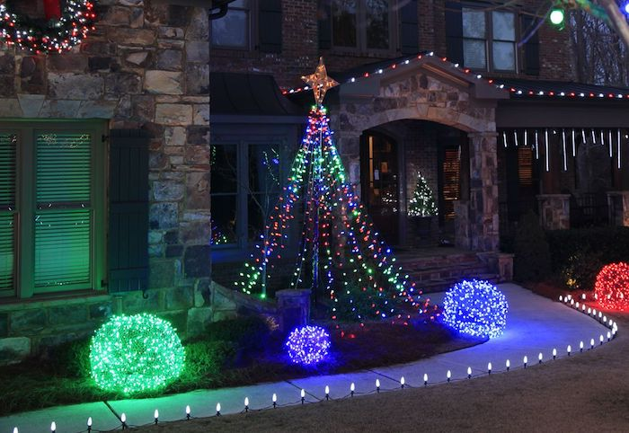 lights along a pathway, leading to a house, bushes on the side, decorated with lights in blue and green, outdoor lighted nativity scene