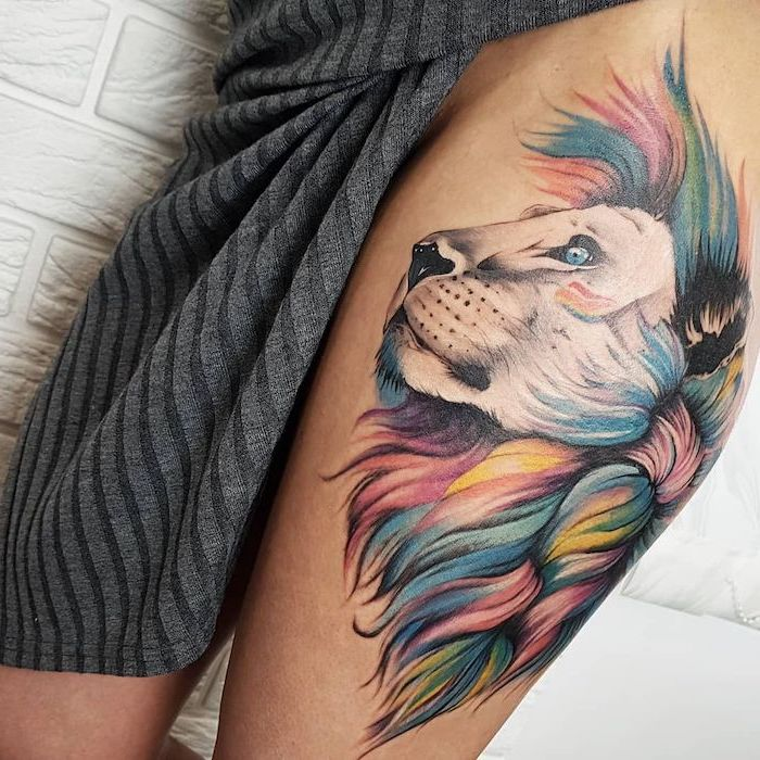 thigh tattoo on woman wearing grey knitted dress, profile of a lion head with colorful mane, lion king tattoo, watercolor tattoo