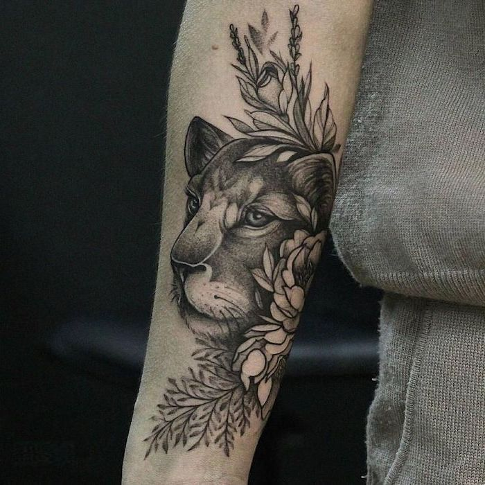 forearm tattoo, lioness head surrounded by flowers, lion hand tattoo, on woman wearing grey blouse