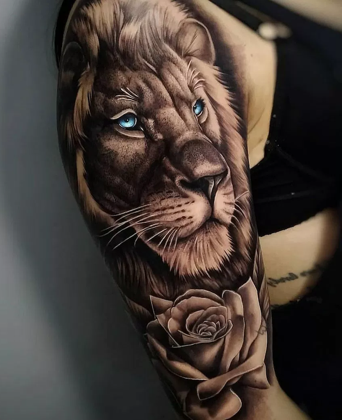lion head with blue eyes, rose underneath, shoulder tattoo, lion tattoo meaning, woman wearing black top
