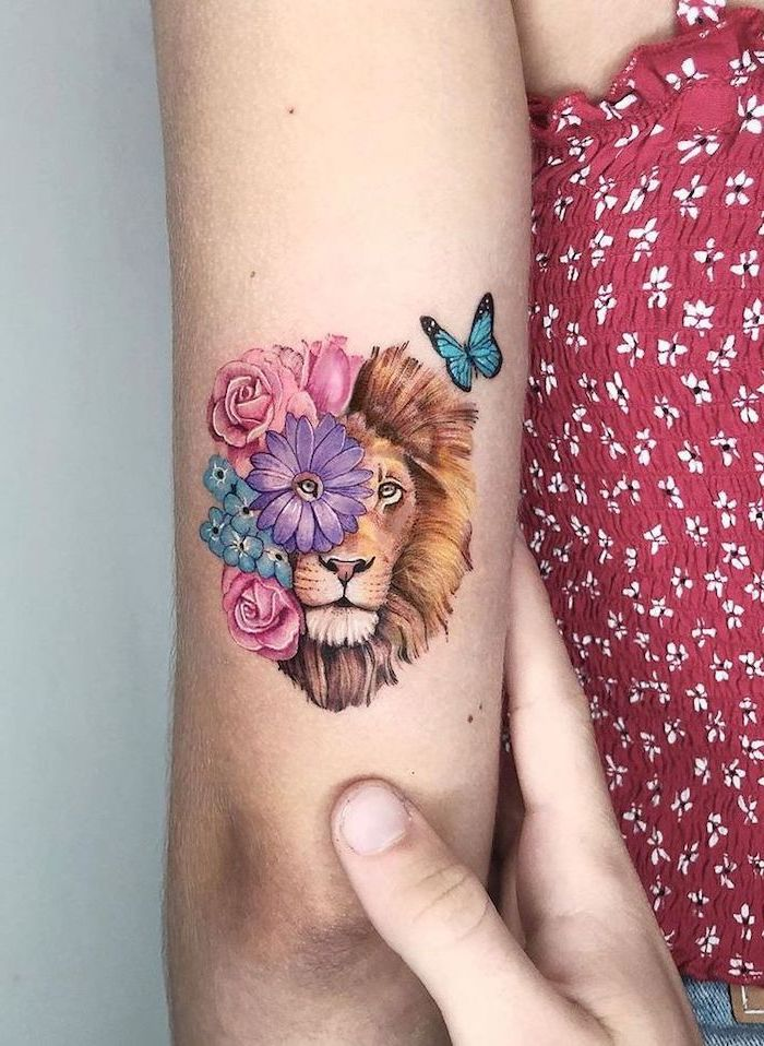 back of arm tattoo, lion tattoo meaning, lion head with colorful flowers surrounding it, blue butterfly in the corner