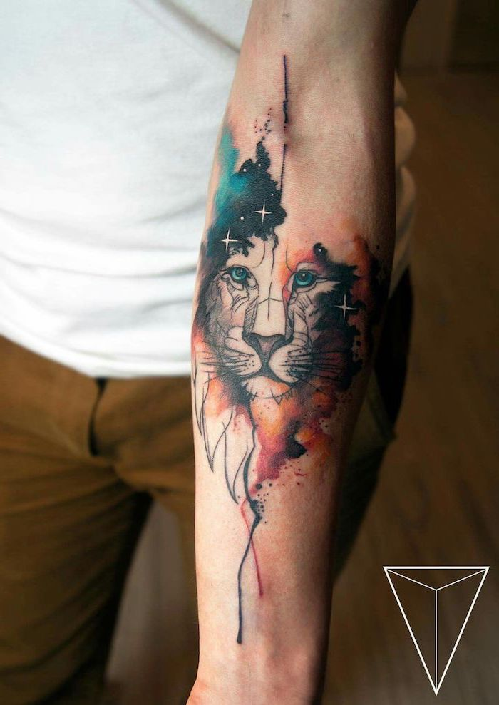 watercolor forearm tattoo, lion tattoo meaning, lion head with blue and orange watercolor mane