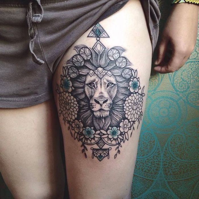 thigh tattoo, mandala tattoo, lion tattoo on arm, lion head with large mane, blue flowers around it, mandala flowers