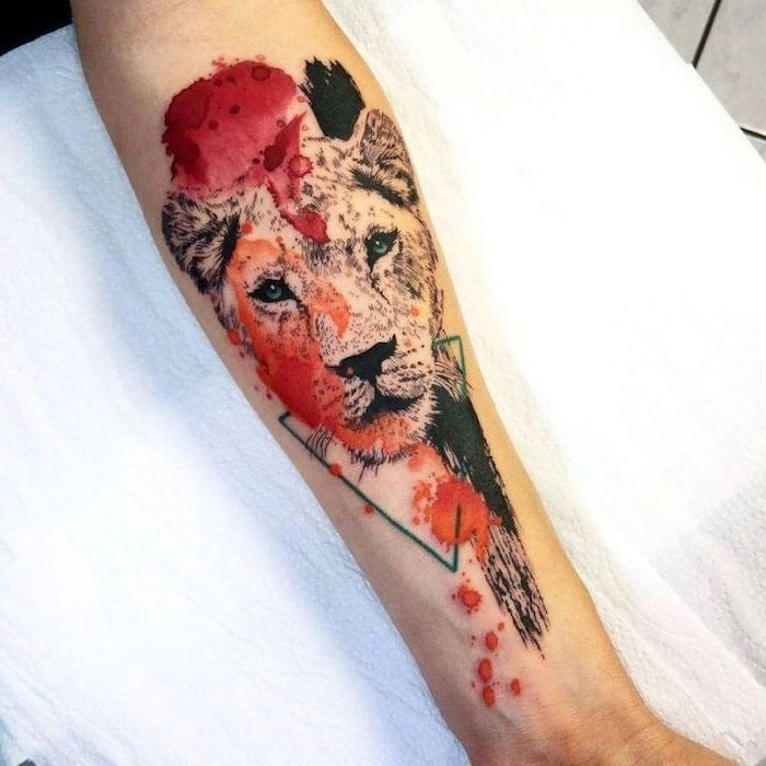 watercolor tattoo, forearm tattoo, lion tattoo on arm, lioness head with red orange and black brush strokes