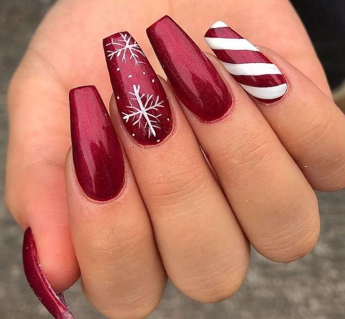 red glitter nail polish, cute nail colors, snowflakes decoration on middle finger, candy cane decoration on pinky