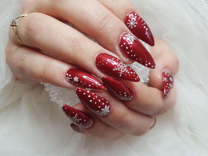 red metallic nail polish, winter nail designs, white snowflakes decorations on each nail, stiletto nails