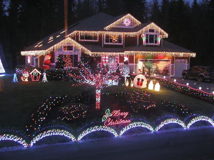two storey house, covered with lights, outdoor lighted nativity scene, lots of lighted figurines in the front yard