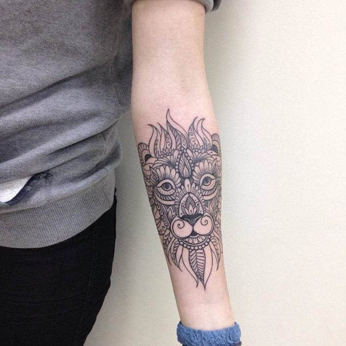 tribal lion tattoo, mandala lion forearm tattoo, on woman wearing grey blouse and black jeans