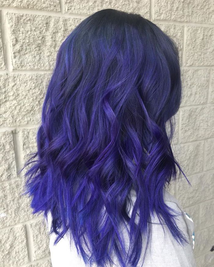 blue and purple balayage, fall blonde hair, woman wearing grey blouse, medium length wavy hair