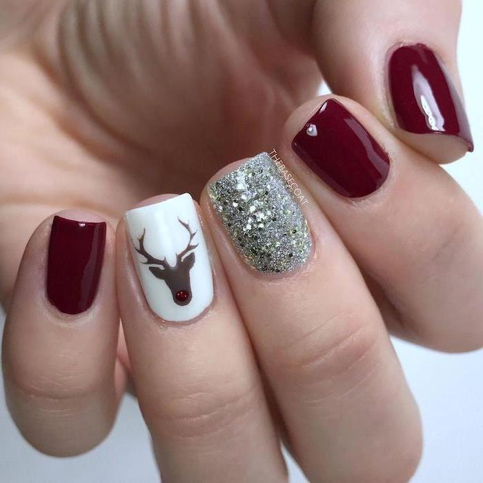 dark red and white nail polish, silver glitter on the middle finger, popular nail colors, reindeer decoration on ring finger
