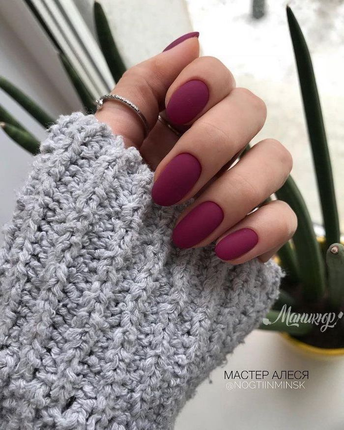 burgundy nail polish, cute nail colors, almond nails, woman wearing grey sweater, rings on thumb and index finger