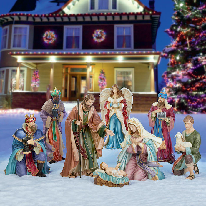 outdoor lighted nativity scene, placed in the snow, in front of a large two storey house, decorated with lights
