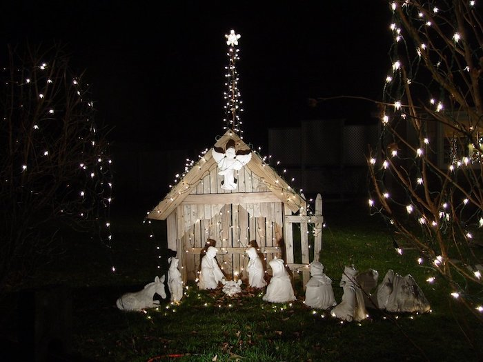 christmas deer decorations, nativity scene made of wood and ceramics, covered with lights, placed in a yard