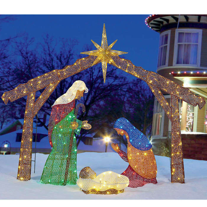 nativity scene with fairy lights, placed in the snow, in front of a house, decorated with lights, christmas deer decorations