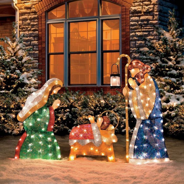nativity scene with lights, christmas deer decorations, placed in the snow, in front of a house, bushes and trees decorated with lights
