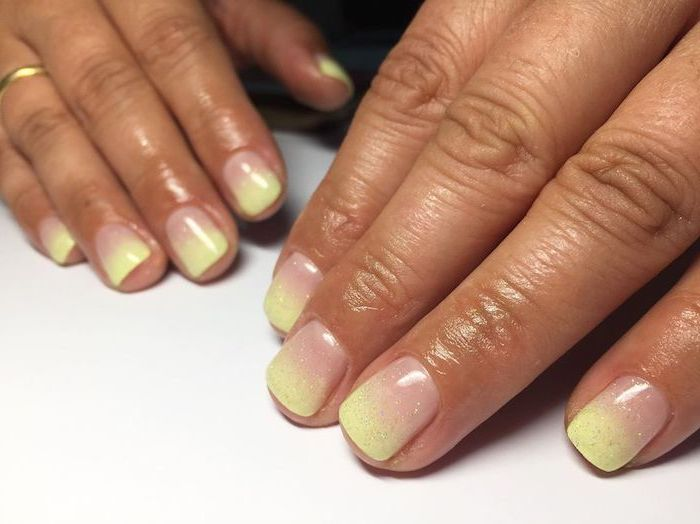 nude to yellow gradient glitter nail polish, ombre coffin nails, short squoval nails, hands placed on white surface