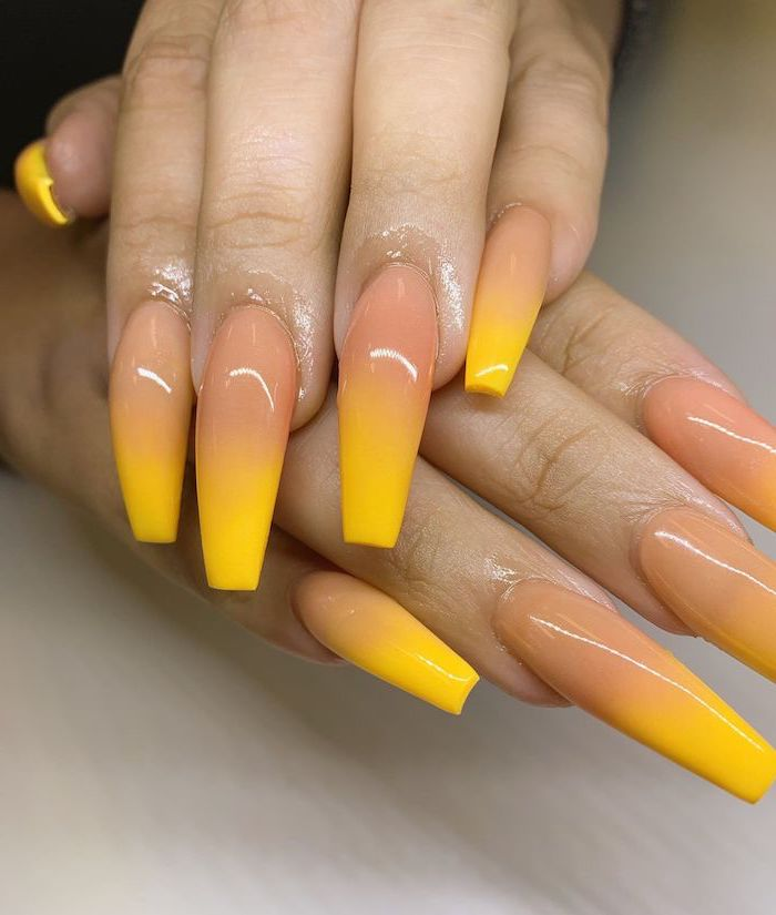 nude to yellow gradient nail polish, ombre nail designs, extra long coffin nails, hands placed on white surface