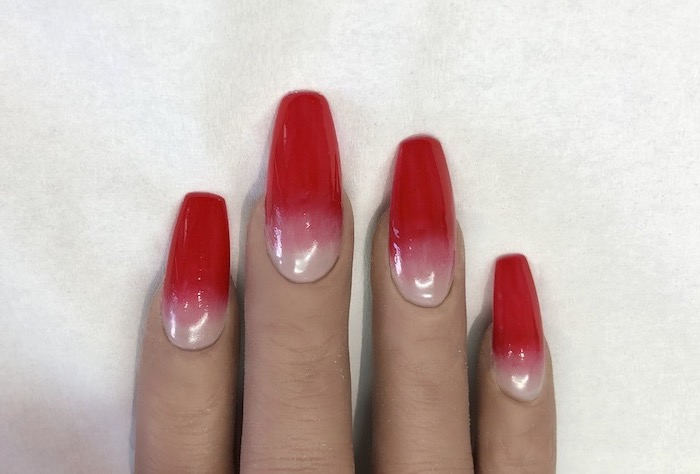 long square nails, nude to red gradient nail polish, ombre nail designs, hand placed on white background