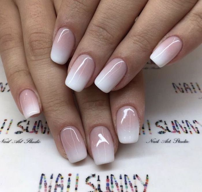 nude to white nail polish, red ombre nails, medium length squoval nails, hand placed on white surface