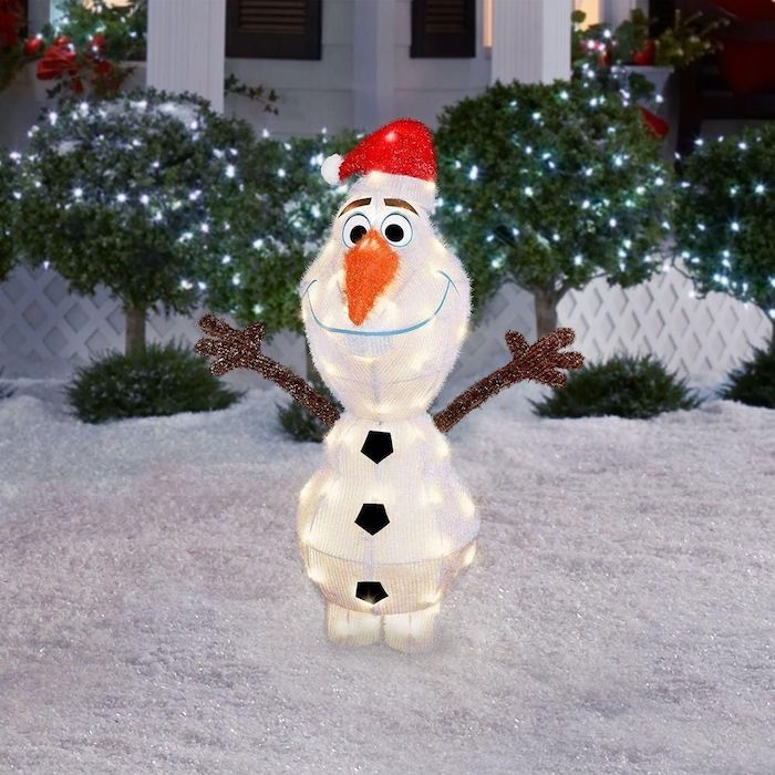 olaf from frozen, figurine with lights inside, christmas deer decorations, placed in the snow, bushes with lights in the background